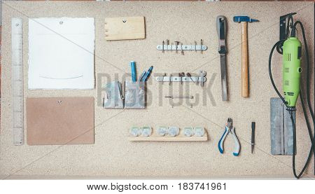 Various working tools hanging on wooden board in workshop.