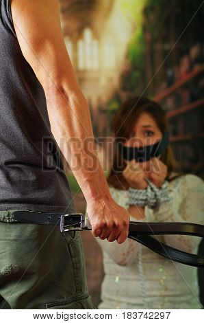 Man holding belt towards terrified tied up young woman in the background