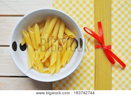 Different types of italian pasta, penne and spaghetti on kitchen table.