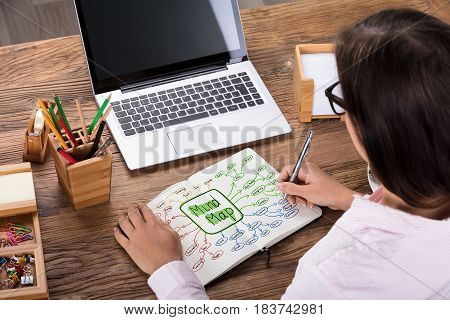 Close-up Of A Businesswoman Drawing Mind Plan On Notebook At Workplace