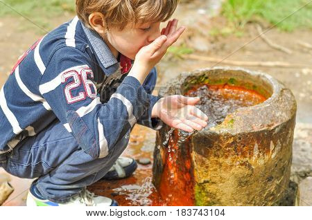 A boy drinks water from a spring