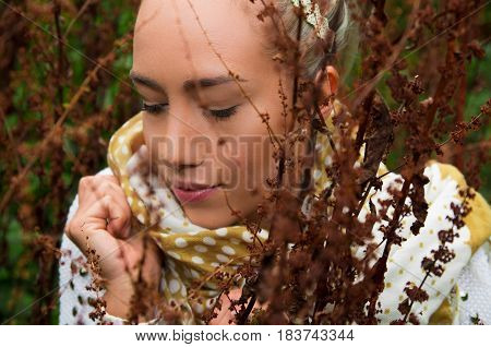 Close up shot of beautiful young latin girl behind some forest weeds