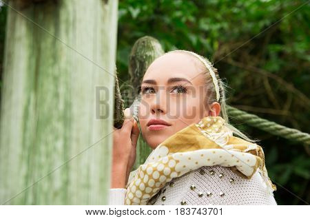 Close up shot if young blond girl sitting in a walking wooden bridge looking peaceful