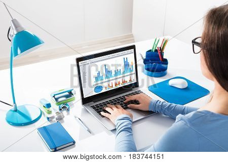 Close-up Of A Businesswoman Looking At Graph On Laptop At Workplace