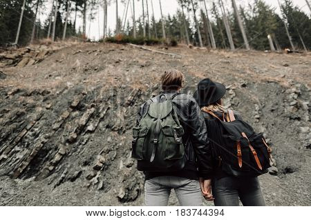 The couple are traveling. Boy and girl with backpacks travel. A man and a woman near the cliff. The couple are back