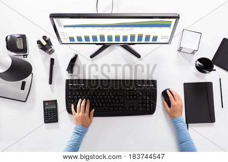 Elevated View Of A Businesswoman Analyzing Graph At Workplace