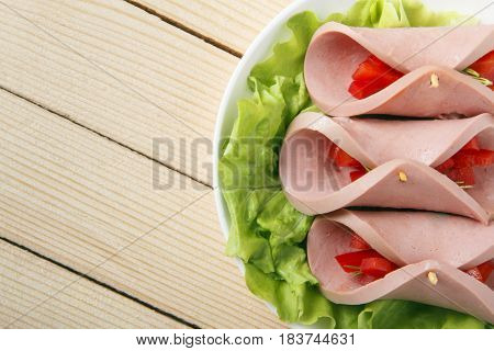 Roll of homemade sausage with vegetables on a wooden background. Space for text