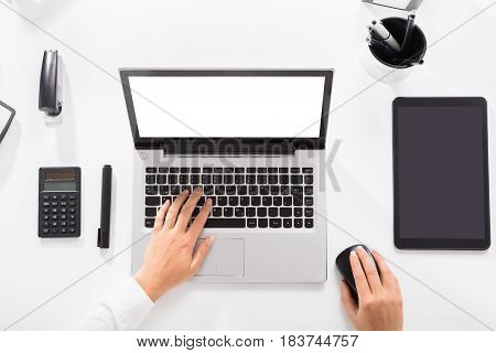 Close-up Of A Woman Working On Laptop On Desk At Workplace