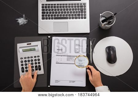 Close-up Of A Businesswoman Looking Invoice Through Magnifying Glass While Calculating