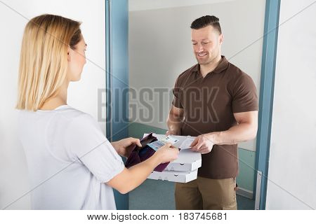 Woman Giving Currency To Pizza Man For Delivering Pizza