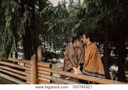 Couple in poncho. The man is dressed in a poncho, a woman dressed in a poncho. Loving couple