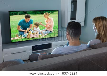Rear View Of A Couple Watching Movie On Television At Home