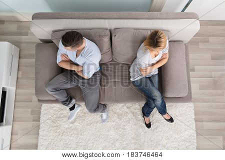 Elevated View Of Upset Couple Sitting On Couch At Home