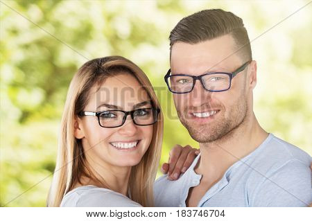 Happy Young Couple With Stylish Eyeglasses Outside