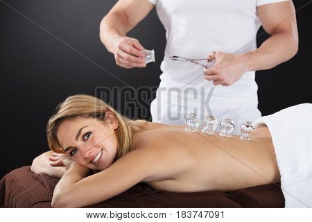 Smiling Young Woman Lying On Front Receiving Cupping Treatment On Back