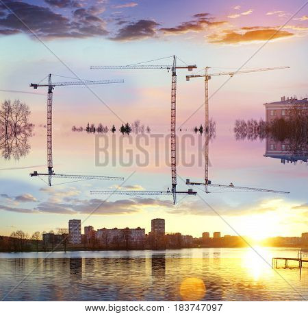Surreal art. Tower cranes against the background of the lake and houses. Upside down. Concept of