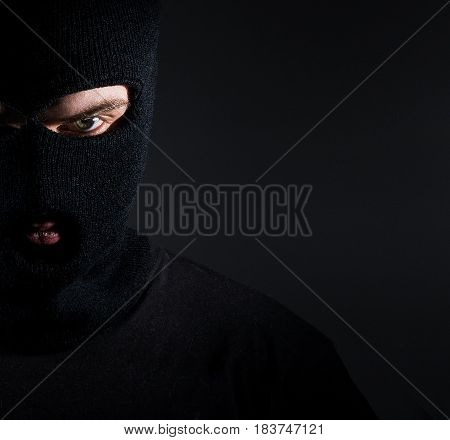 Man in a balaclava portrait a thief on a dark