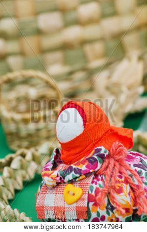 Trade in the market, the traditional talisman dolls without faces on the background of wicker baskets. Selective focus.