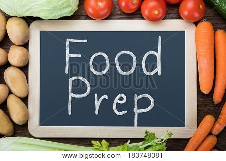 Elevated View Of Fresh Organic Vegetables With Food Preparation Words Written On Slate