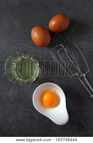 Egg beater and broken egg on dark background, top view