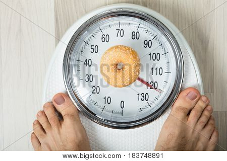 Close-up Of A Person Measuring Weight With Donut On Weighing Scale