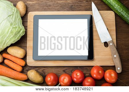 Blank Digital Tablet On Chopping Board With Fresh Vegetables On Table