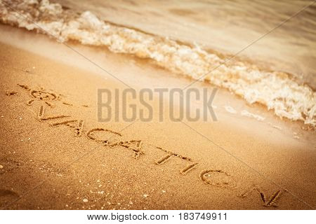 Holidays summer concept. The word vacation written in the sand on beach.
