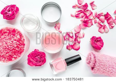 manicure set with nail polish and rose cream on white table background top view