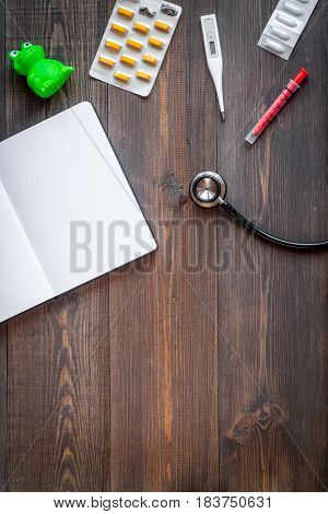 stethoscope, thermometer, opened notebook on children's doctor office wooden desk background top view mockup