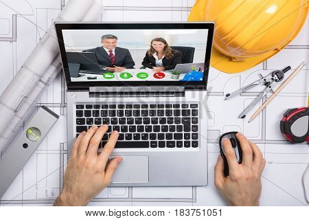 Elevated View Of A Architect Chatting With Her Colleague On Video Conference At Workplace