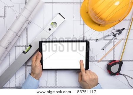 Close-up Of A Male Architect Touching The Screen Of Digital Tablet On Blueprint With Equipments