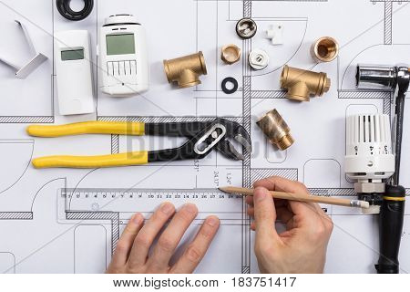 Close-up Of An Architect Working On Blueprint With Radiator Fixtures And Work Tool