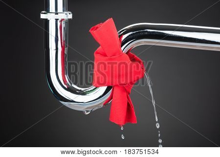 Red Cloth Tied On Leakage Pipe Over The Gray Background
