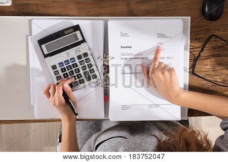Close-up Of A Businessperson Calculating Invoice Using Calculator On Office Desk