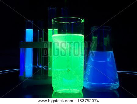 Photo composition of a laboratory bottles and test-tubes with glowing liquids standing on a glass table under ultraviolet lights.