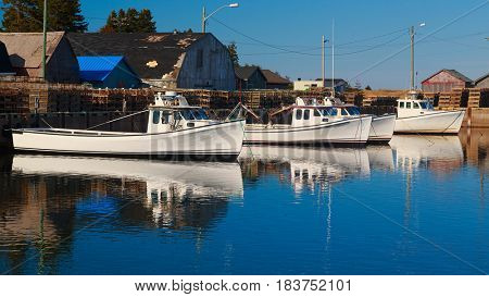 Commercial fishing boats at a wharf in rural Prince Edward Island, Canada.