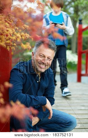 Portrait of handsome happy smiling man posing in spring Japanese garden with his son using smartphone ion background