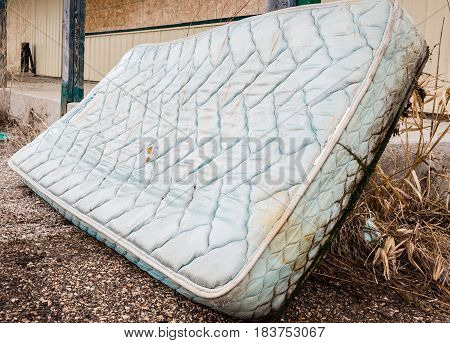 horizontal image of an old worn out water logged mattress leaning against a railing in the summer time