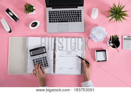 Elevated View Of A Businesswoman Calculating Invoice Using Calculator On Pink Desk