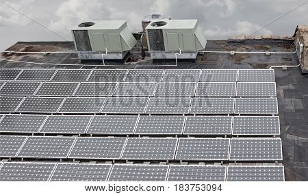 horizontal image of solar sun panels on the roof of a tall building.