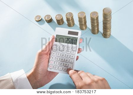 Person Calculating Savings On Calculator And Stacked Coins On Blue Desk
