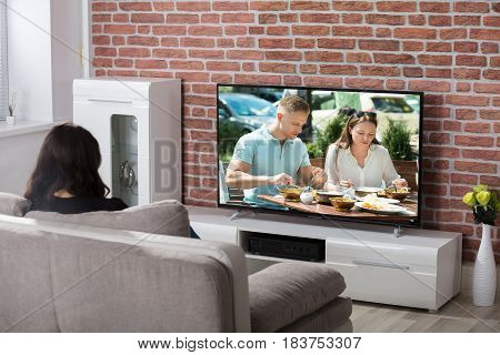 Young Woman Sitting On Couch Watching Television At Home