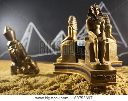 Ancient old metal statuettes standing on a sand surface with a blackboard drawn background.