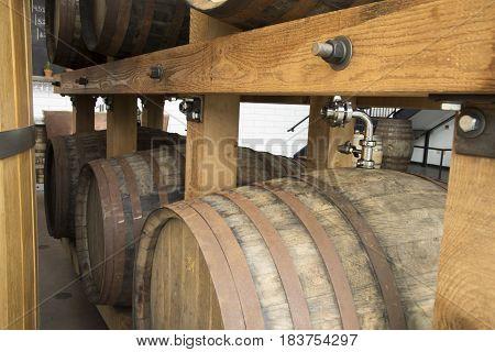 Taps on wooden beer kegs in rack.