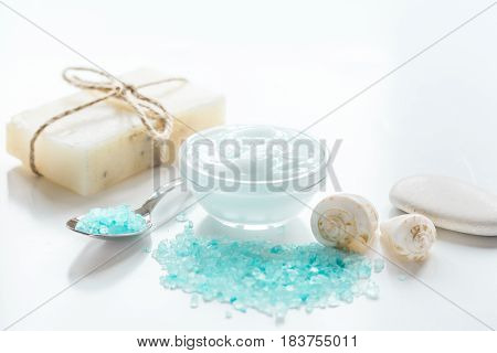 homemade spa composition with blue sea salt and natural soap on white desk background
