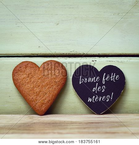 closeup of a heart-shaped cookie and a heart-shaped black signboard with the text bonne fette des meres, happy mothers day written in french, against a pale green rustic wooden background