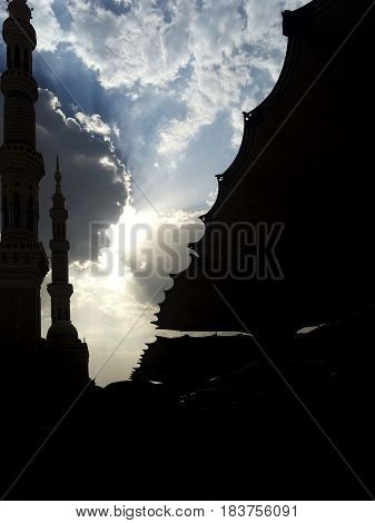 Beautiful sky view with silhouette of the Prophet Mosque minaret and giant umbrella.