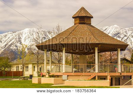 Gazebo In Town Park With Snow Covered Mountains In Background