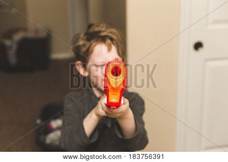 Young boy aiming a toy gun at the camera.