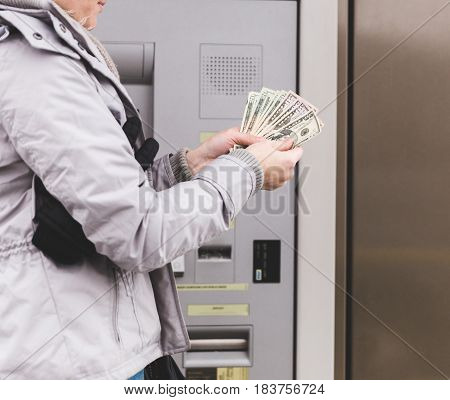 Woman counting money while standing next to an ATM (automated teller machine).
